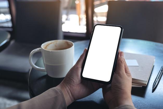Modellbild der hände, die ein schwarzes mobiltelefon mit leerem bildschirm halten und verwenden