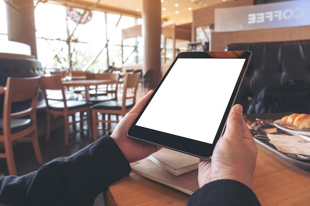 Modellbild der hände, die schwarzen tablett-pc mit leerem bildschirm mit notizbuch und brot auf holztisch im café halten