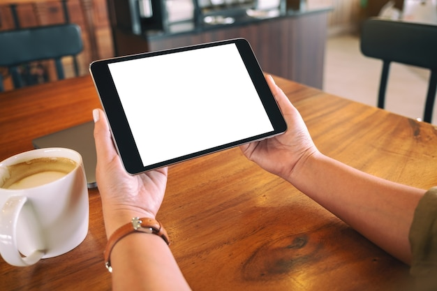 Modellbild der hände, die schwarzen tablett-pc mit leerem weißen bildschirm horizontal mit kaffeetasse auf holztisch halten