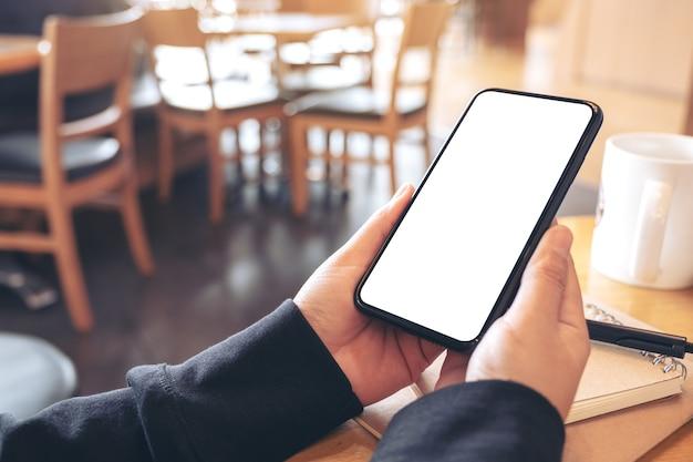 Modellbild der hände, die schwarzes handy mit leerem weißen bildschirm im café halten