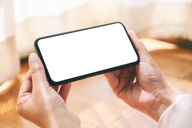 Modellbild der hände, die schwarzes mobiltelefon mit leerem desktop-bildschirm horizontal halten und verwenden