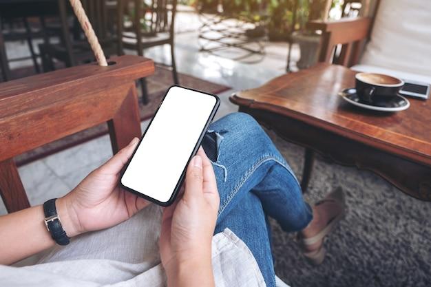 Modellbild der hände, die schwarzes mobiltelefon mit leerem weißen bildschirm halten, während im café sitzen