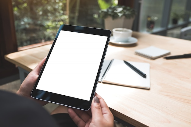 Modellbild der hände einer frau, die schwarzen tablett-pc mit weißem leerem bildschirm mit notizbuch und kaffeetasse auf tisch halten
