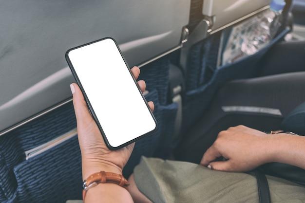 Modellbild der hand der frau, die ein schwarzes smartphone mit leerem desktop-bildschirm in der kabine hält