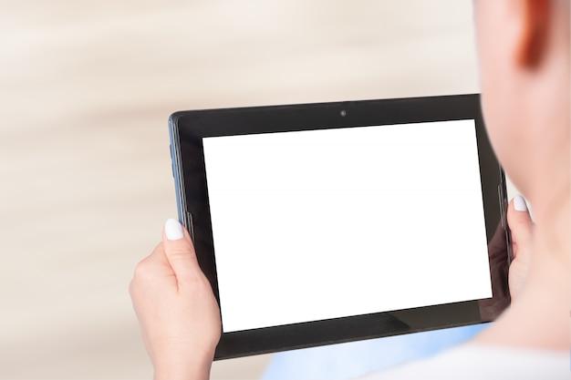 Modellbild der hand der frau, die weißen tablett-pc hält. frau sitzt und hält weiße bildschirmmodelltafel