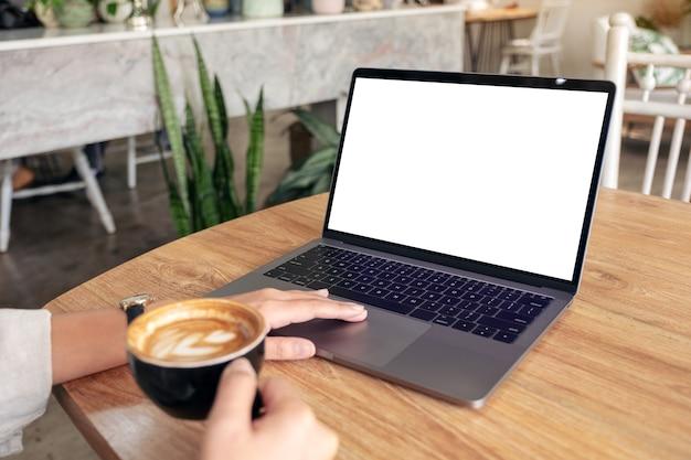 Modellbild der hand der frau unter verwendung und berühren des modell-laptop-touchpads beim kaffeetrinken