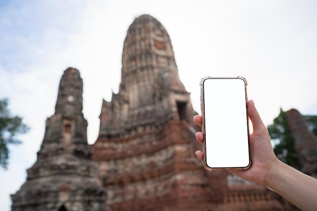 Modellbild der hand, die handy mit leerem weißen bildschirm mit pagode hält