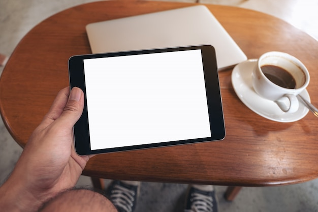Modellbild der hand, die schwarzen tablett-pc mit leerem weißen desktop-bildschirm mit laptop und kaffeetasse auf holztisch hält