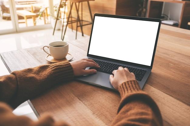 Modellbild der hand einer frau, die auf laptop mit leerem weißem desktop-bildschirm mit kaffeetasse auf holztisch verwendet und tippt