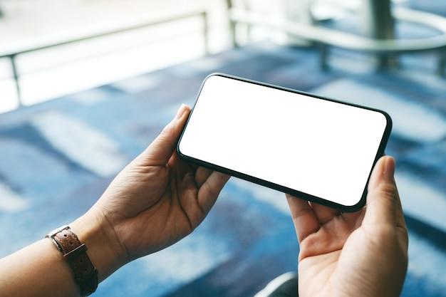 Modellbild der hand einer frau, die ein schwarzes mobiltelefon mit einem leeren weißen desktop-bildschirm hält