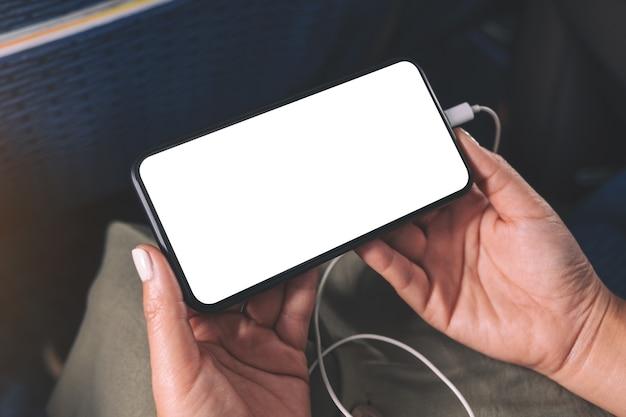 Modellbild der hand einer frau, die ein schwarzes smartphone mit leerem desktop-bildschirm und kopfhörer in der kabine hält