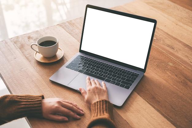 Modellbild der hand einer frau, die laptop-touchpad mit leerem weißem desktop-bildschirm mit kaffeetasse auf holztisch verwendet und berührt