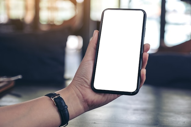 Modellbild der hand einer frau, die schwarzes handy mit leerem desktop-bildschirm hält