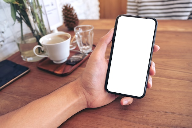 Modellbild der hand eines mannes, der schwarzes handy mit leerem bildschirm mit frau im café hält