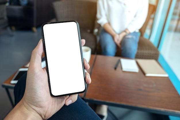 Modellbild der hand eines mannes, die schwarzes handy mit leerem weißen bildschirm mit frau hält, die im café sitzt