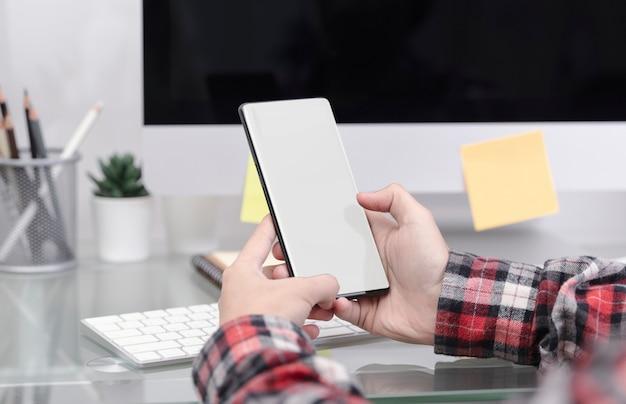 Modellbild der hand handy mit leerem bildschirm auf bürotisch halten. soziales netzwerk auf ihrem smartphone-konzept.