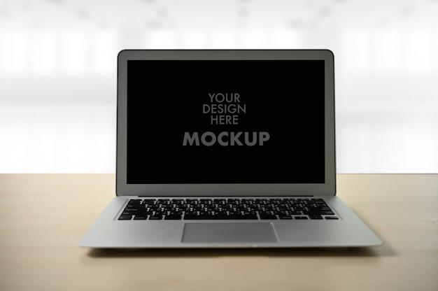 Modellbild des geschäfts-laptops mit leerem bildschirm auf tabelle
