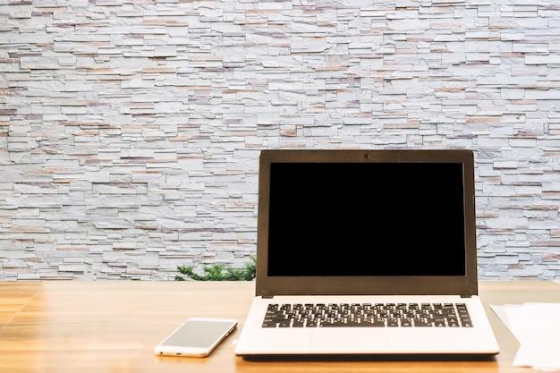 Modellbild des laptops mit leerem schwarzem schirm, smartphone, auf holztisch