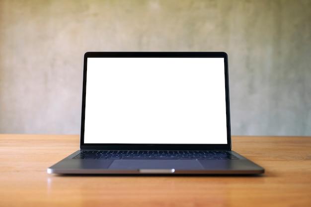 Modellbild des laptops mit leerem weißem desktop-bildschirm auf holztisch mit betonwandhintergrund