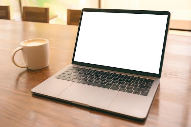 Modellbild des laptops mit leerem weißen desktop-bildschirm mit kaffeetasse auf holztisch