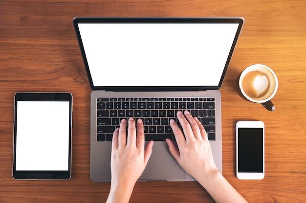 Modellbild des laptops, tablette, intelligentes telefon auf holztisch mit kaffeetasse