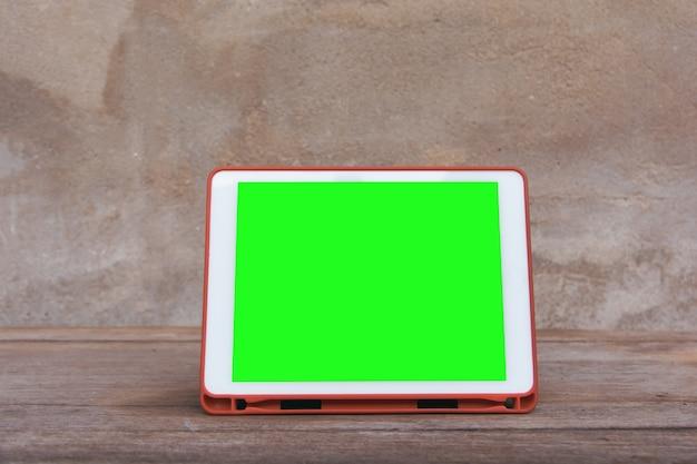 Modellbild des weißen tabletten-pc mit leerem grünem tischplattenschirm auf holztisch