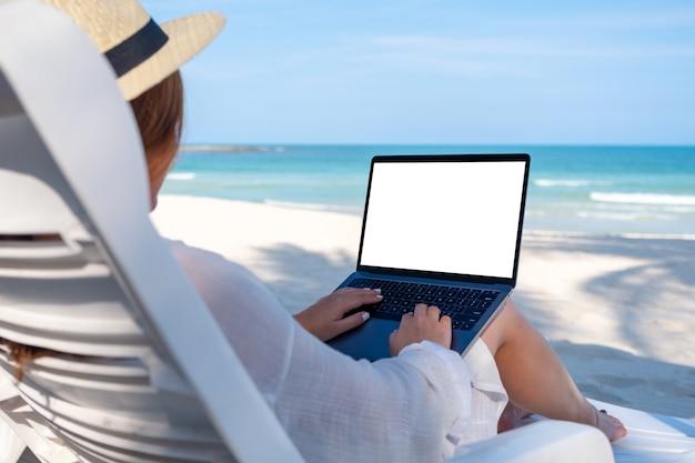 Modellbild einer frau, die auf laptop-computer mit leerem desktop-bildschirm verwendet und tippt, während sie sich auf strandkorb am strand niederlegt