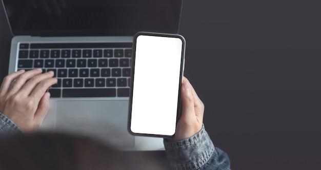 Modellbild einer frau, die ein mobiltelefon mit leerem bildschirm verwendet und am laptop auf dem bürotisch arbeitet