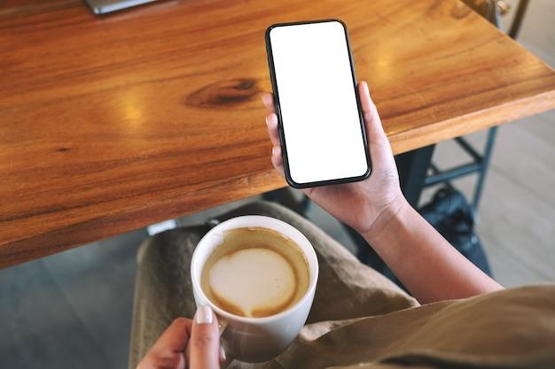 Modellbild einer frau, die ein schwarzes handy mit leerem desktop-bildschirm hält, während sie kaffee trinkt
