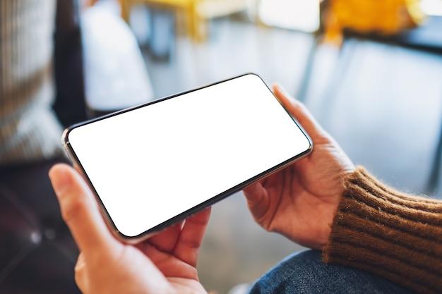 Modellbild einer frau, die ein schwarzes handy mit leerem desktop-bildschirm hält