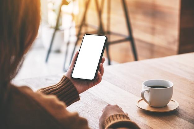 Modellbild einer frau, die ein schwarzes handy mit leerem desktop-bildschirm mit kaffeetasse auf dem tisch hält