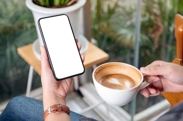 Modellbild einer frau, die ein schwarzes mobiltelefon mit leerem desktop-bildschirm hält und benutzt, während sie kaffee im café trinkt