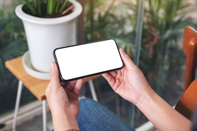 Modellbild einer frau, die ein schwarzes mobiltelefon mit leerem desktop-bildschirm im café hält und verwendet