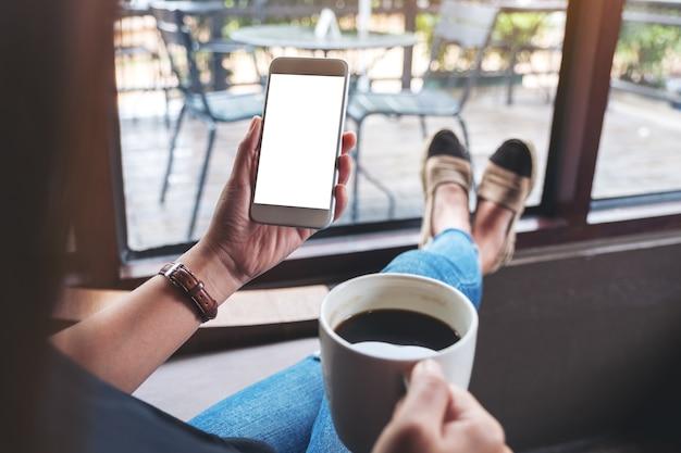 Modellbild einer frau, die ein weißes handy mit leerem desktop-bildschirm hält, während sie im café sitzt und kaffee trinkt