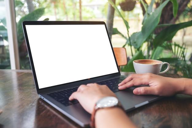 Modellbild einer frau, die einen laptop mit leerem weißem desktop-bildschirm mit kaffeetasse auf holztisch im büro verwendet und tippt