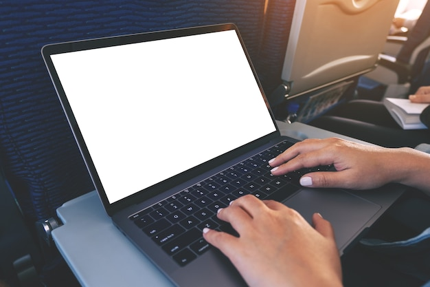 Modellbild einer frau, die einen laptop mit leerem weißem desktop-bildschirm verwendet und tippt, während sie in der kabine sitzt
