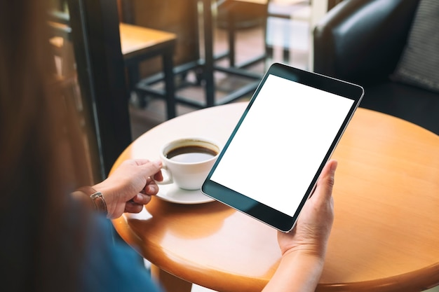Modellbild einer frau, die einen schwarzen tablet-pc mit leerem weißen bildschirm hält, während sie kaffee trinkt