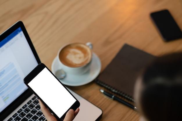 Modellbild einer frau, die handy mit leerem schwarzem schirm im modernen dachbodencafé hält