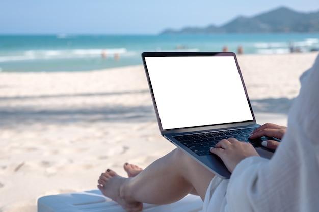 Modellbild einer frau, die laptop-computer mit leerem desktop-bildschirm hält und verwendet, während sie auf strandkorb am strand niederlegt