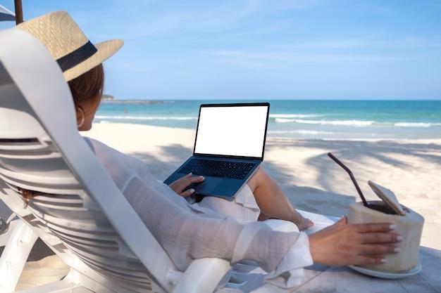 Modellbild einer frau, die laptop-computer mit leerem desktop-bildschirm hält und verwendet, während sie sich auf strandkorb legt und kokosnusssaft am strand trinkt