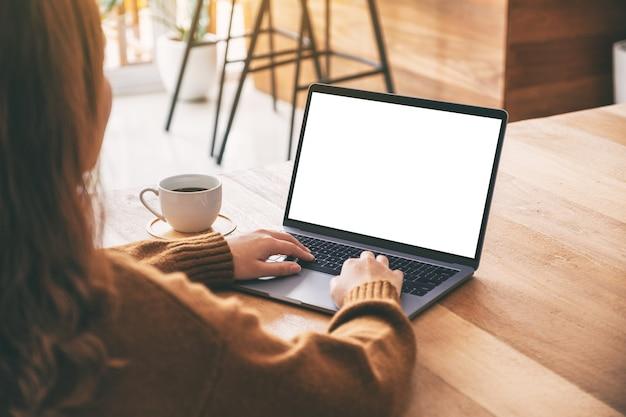 Modellbild einer frau, die laptop-computer-tastatur mit leerem weißem desktop-bildschirm mit kaffeetasse auf holztisch verwendet und tippt