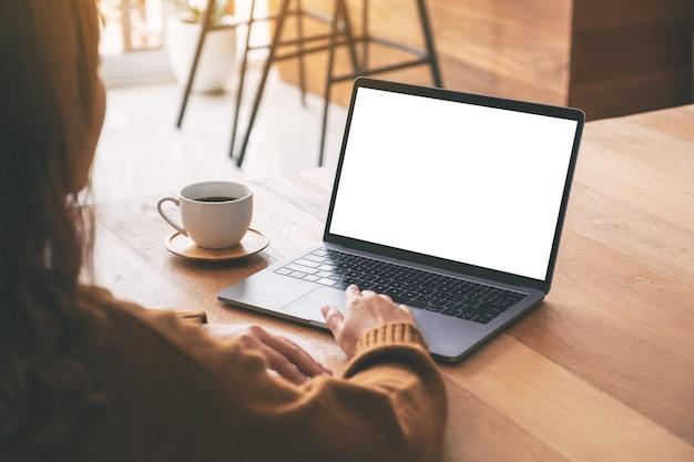 Modellbild einer frau, die laptop-touchpad mit leerem weißem desktop-bildschirm mit kaffeetasse auf holztisch verwendet und berührt