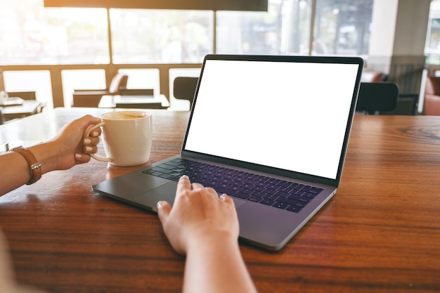 Modellbild einer frau, die laptop-touchpad mit leerem weißen desktop-bildschirm auf holztisch beim kaffeetrinken verwendet und berührt