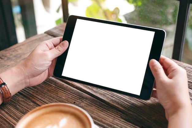 Modellbild einer frau, die schwarzen tablet-pc mit leerem weißem desktop-bildschirm mit kaffeetasse auf holztisch hält