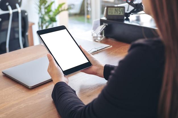 Modellbild einer frau, die schwarzen tablet-pc mit leerem weißen desktop-bildschirm hält und verwendet
