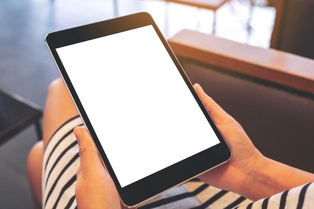 Modellbild einer frau, die schwarzen tablett-pc mit leerem weißen desktop-bildschirm sitzt und hält