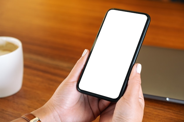Modellbild einer frau, die schwarzes handy mit leerem desktop-bildschirm mit laptop und kaffeetasse auf dem tisch hält