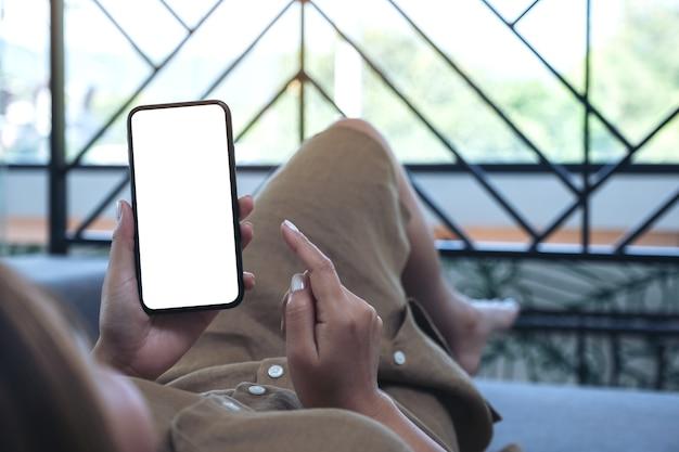 Modellbild einer frau, die schwarzes mobiltelefon mit leerem weißem desktop-bildschirm hält, während im wohnzimmer mit dem gefühl entspannt liegt