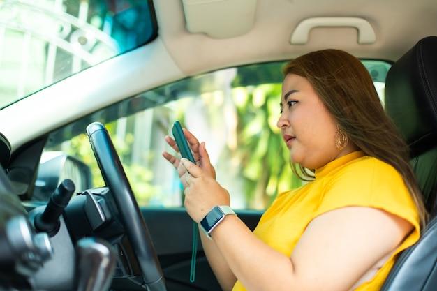 Modellbild einer frau, die smartphone mit leerem bildschirm verwendet. schöne fette frau, die ein auto fährt