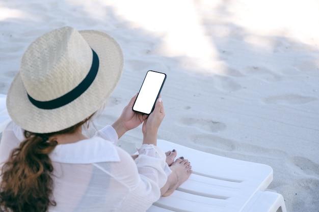 Modellbild einer frau, die weißes handy mit leerem desktop-bildschirm hält, während sie auf strandkorb am strand niederlegt